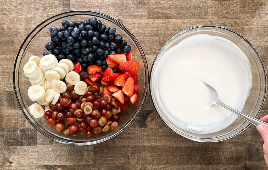A bowl of dairy-free yogurt sauce and a large bowl of assorted fruits.