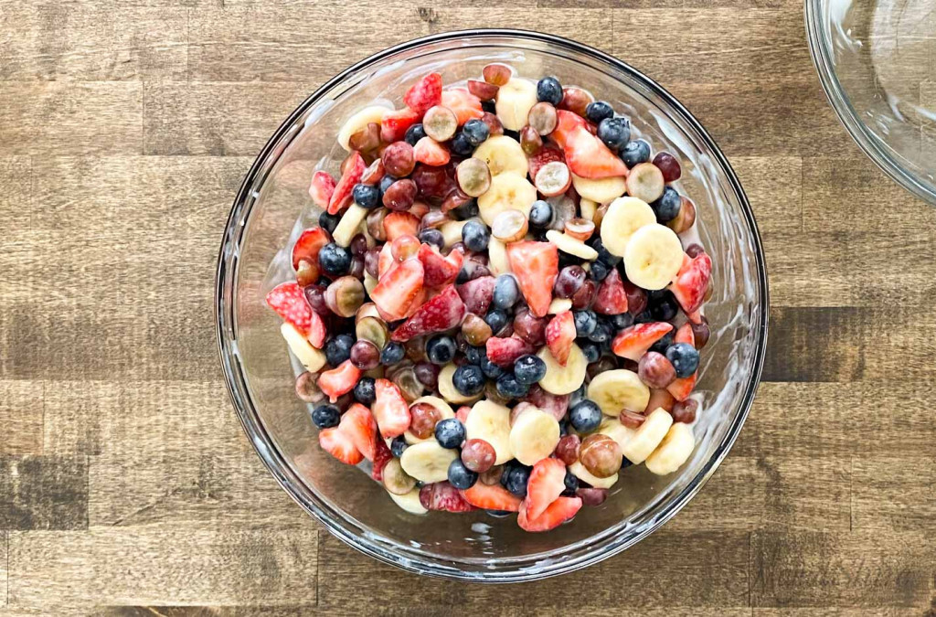 A big bowl of fruit salad that has a dairy-free yogurt sauce over it.