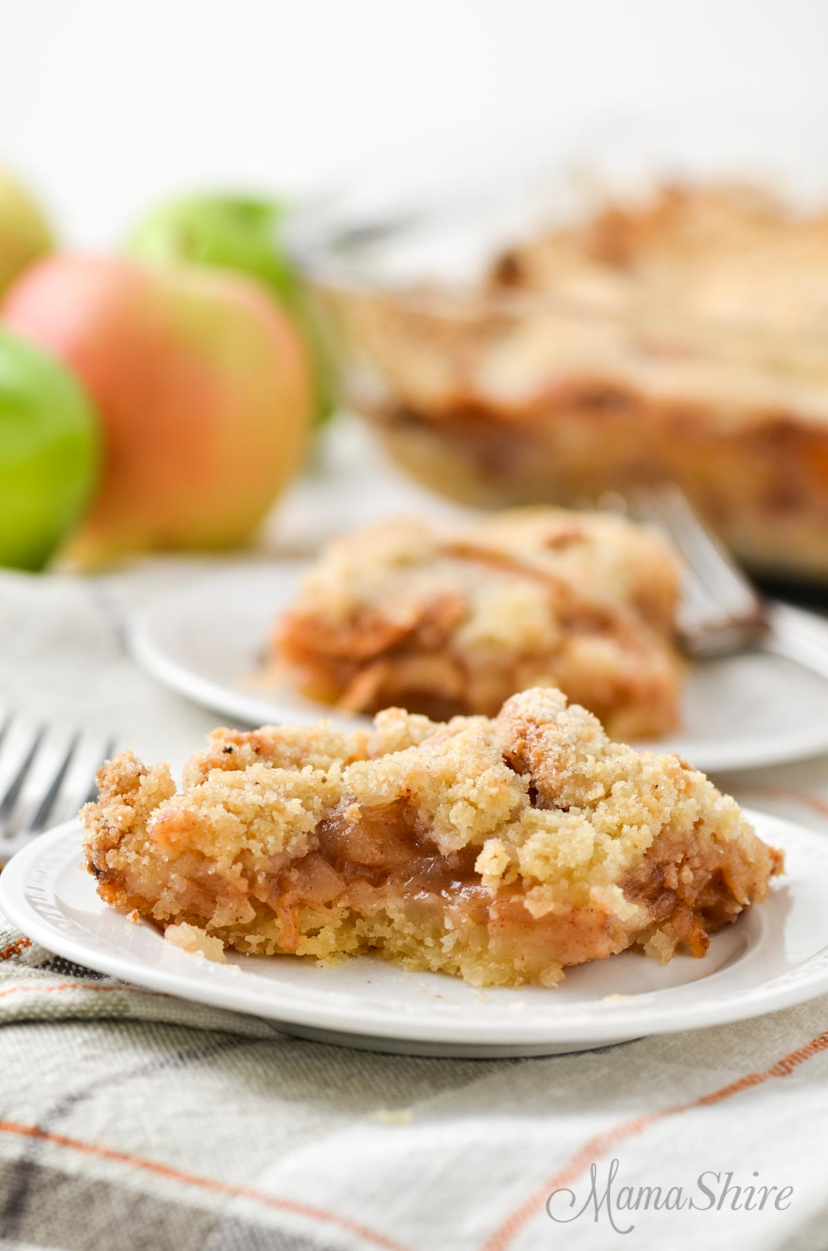 Gluten-free apple slab pie on a white plate with a few apples in the background.