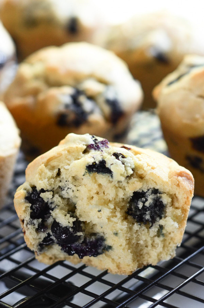 A gluten-free blueberry muffin cut in half so you can see the texture and blueberries.