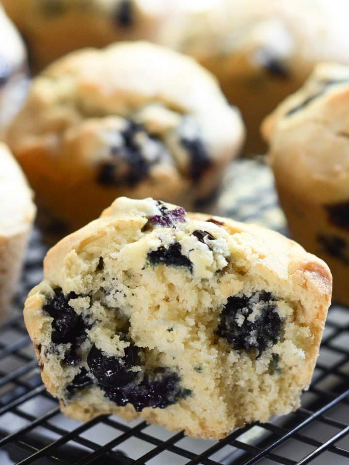 A tender and moist gluten-free blueberry muffin that has been cut in half and it cooling on a wire rack.
