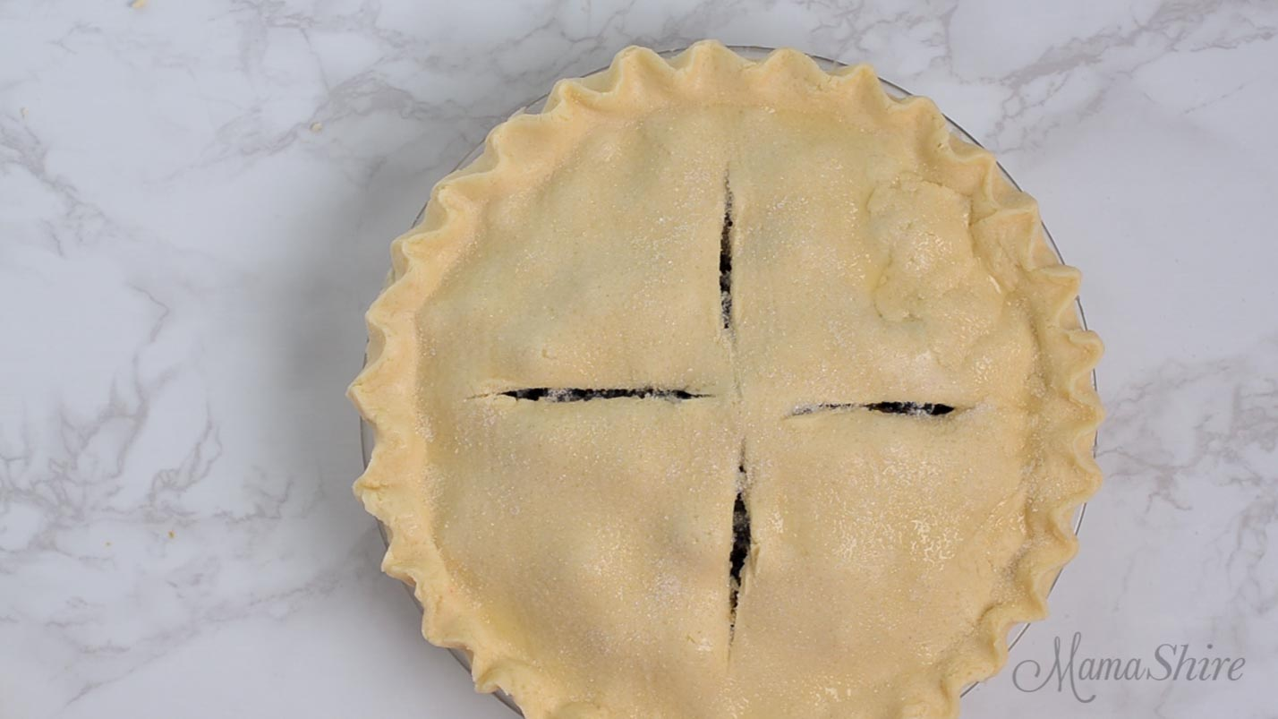 Unbaked pie with four slits cut in the top crust.