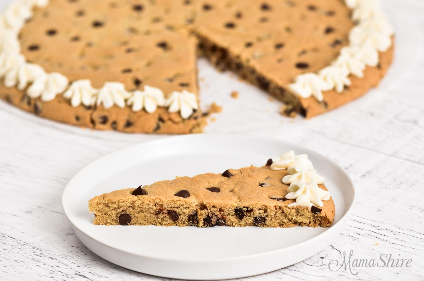 Cookie cake with icing and chocolate chips.