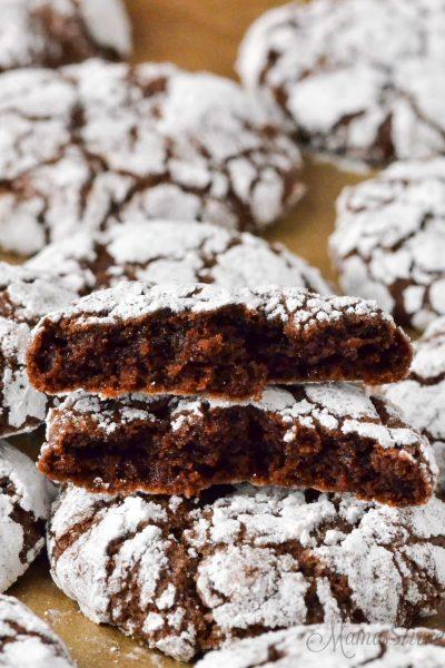 A chocolate crinkle cookie broken in half.