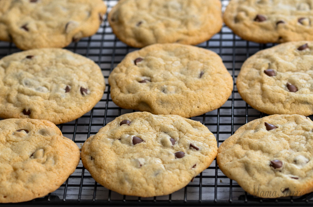 Freshly baked gluten-free chocolate chip cookies cooling on a wire rack.