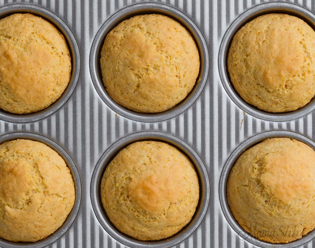 A muffin tin with freshly baked corn muffins.