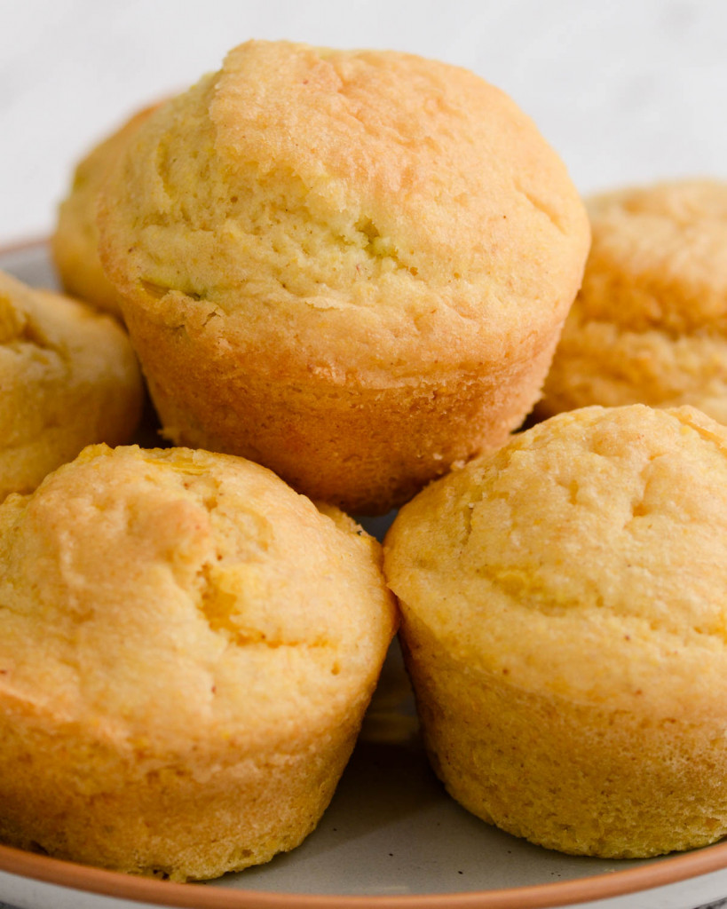 Several gluten-free corn muffins on a plate.