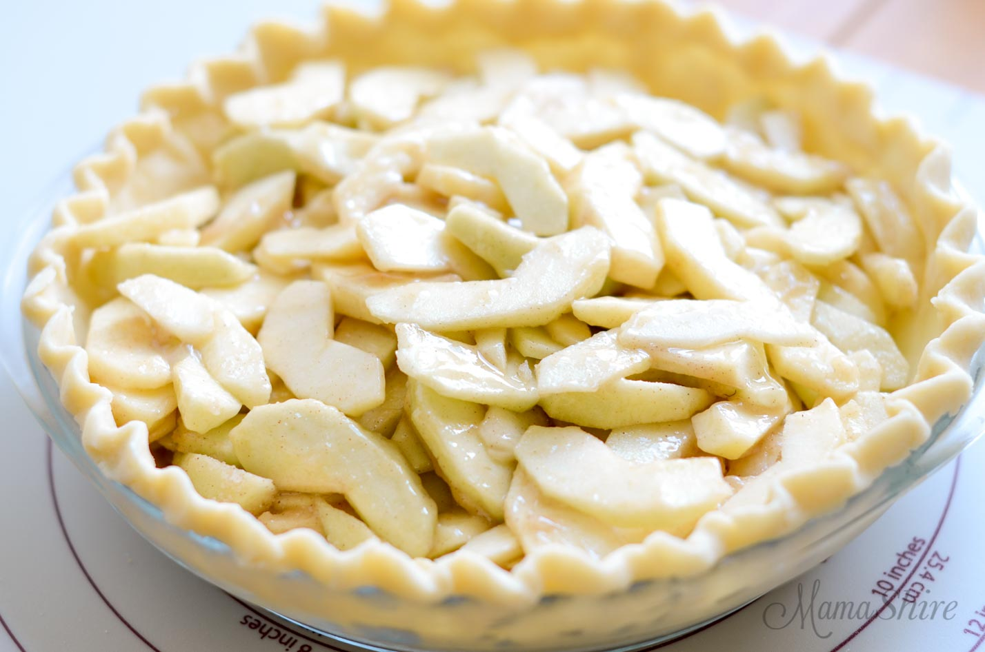A uncooked pie crust in a pie pan with a sliced apple filing.