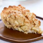 One slice of a Dutch apple pie made from a gluten-free recipe. It has a streusel topping on top of the apples instead of a second crust.