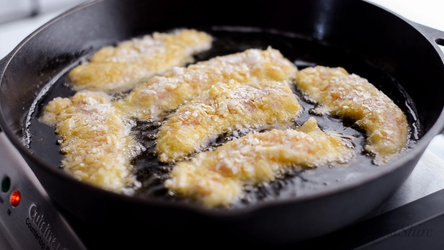 Chicken tenders frying in an iron skillet.