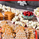 A Christmas table with gingerbread cookies, popcorn, and cranberries.