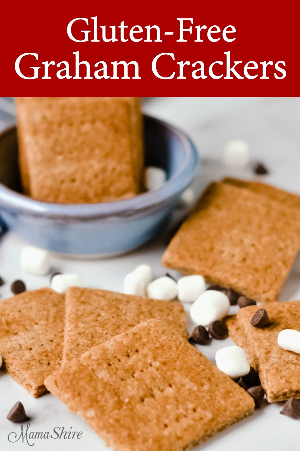 Graham crackers, mini marshmallows, dairy-free chocolate chips all scattered on a marble background. Crackers made with a homemade gluten-free graham cracker recipe.