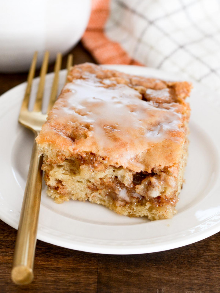 A piece of delicious gluten-free honey bun cake on a white dessert plate with a gold colored fork.