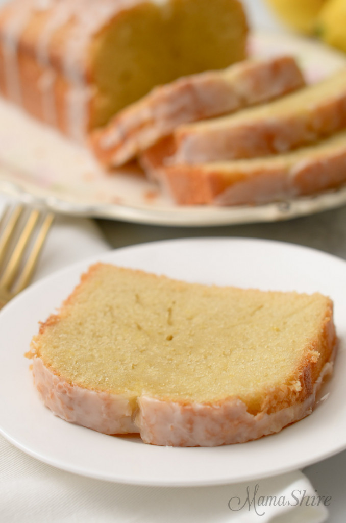 A slice of gluten-free lemon loaf with the rest of the loaf in the background.