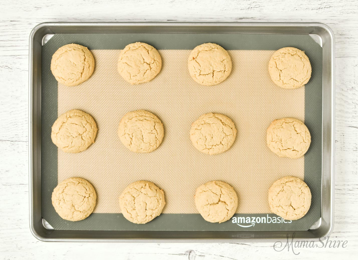 Fresh baked cookies on a baking sheet with a silicone mat.