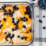 Peaches and blueberries baked together in a cobbler.
