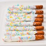Gluten-free pretzel rods with icing and sprinkles.