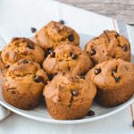 Several pumpkin chocolate chip muffins on a white serving plate. Made from a gluten-free and dairy-free recipe.