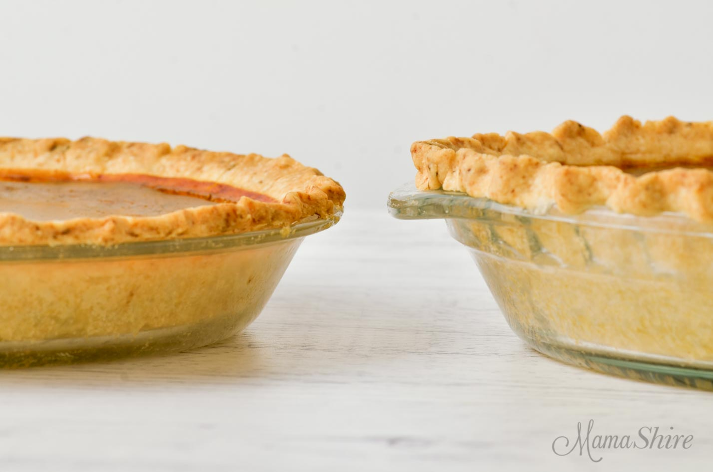 Two pie pans - one shallow and one deeper. Both have gluten-free pumpkin pie in them.