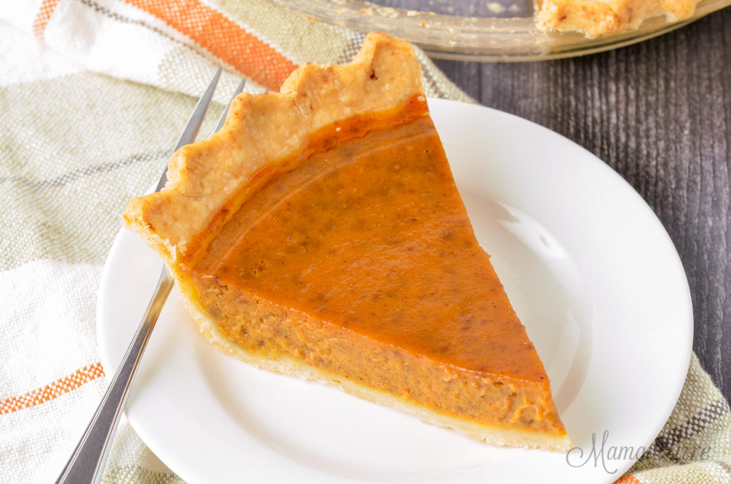 A slice of dairy-free pumpkin pie on a white plate.