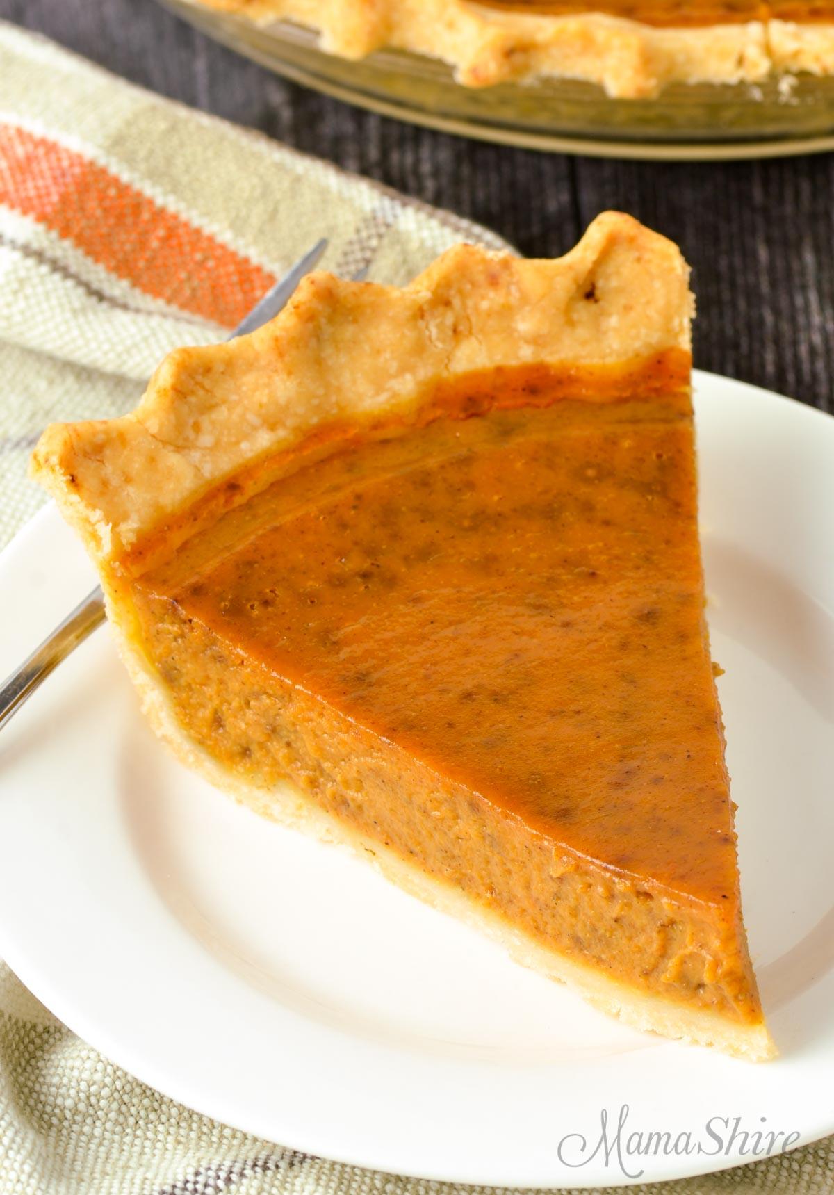 A slice of gluten-free pumpkin pie on a white plate.