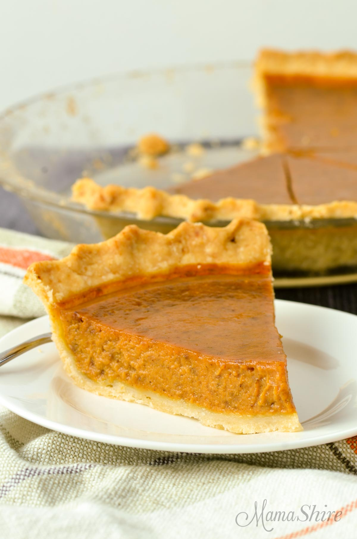 Gluten-free pumpkin pie on a white plate with a half-eaten pie in the background.