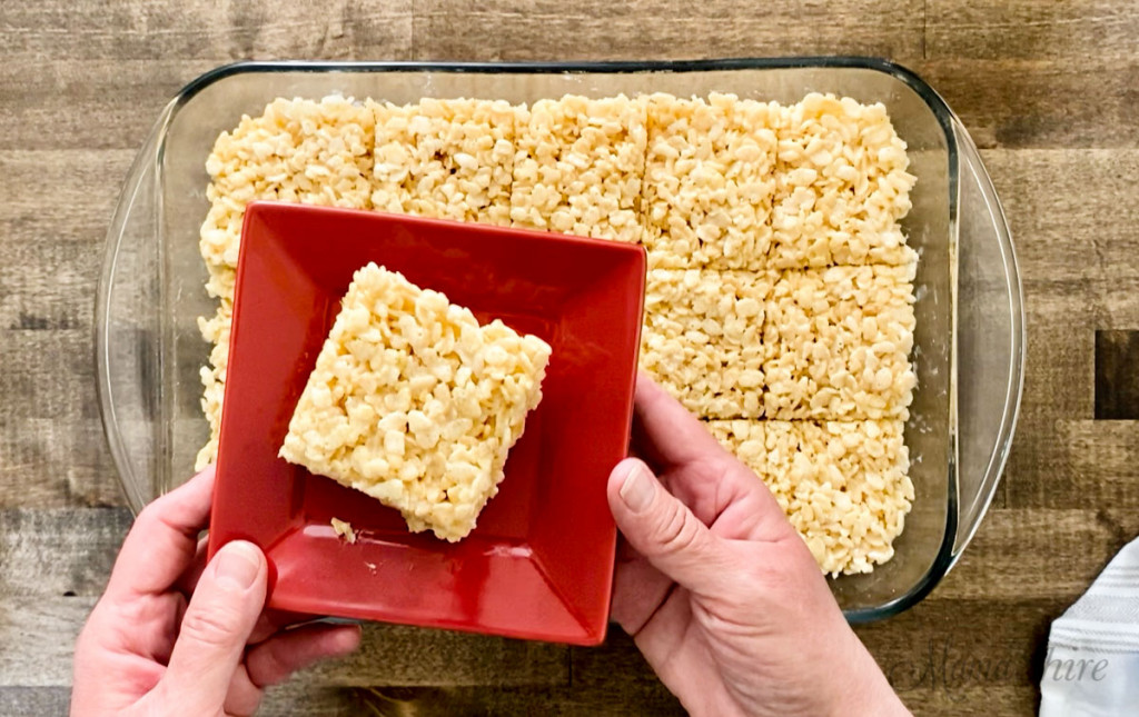 A single serving of gluten-free rice krispie treats on a small red dessert plate.