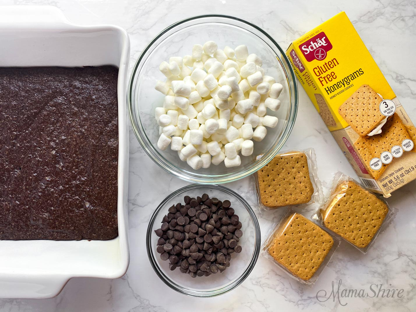 Ingredients for s'mores brownies - freshly baked gluten-free brownies, a bowl of marshmallows, gluten-free and dairy-free chocolate chips, and a pack of Schar's gluten-free graham crackers.