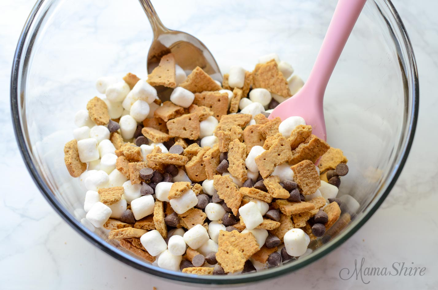 A mixing bowl with crushed graham cracker, chocolate chips, and marshmallows.