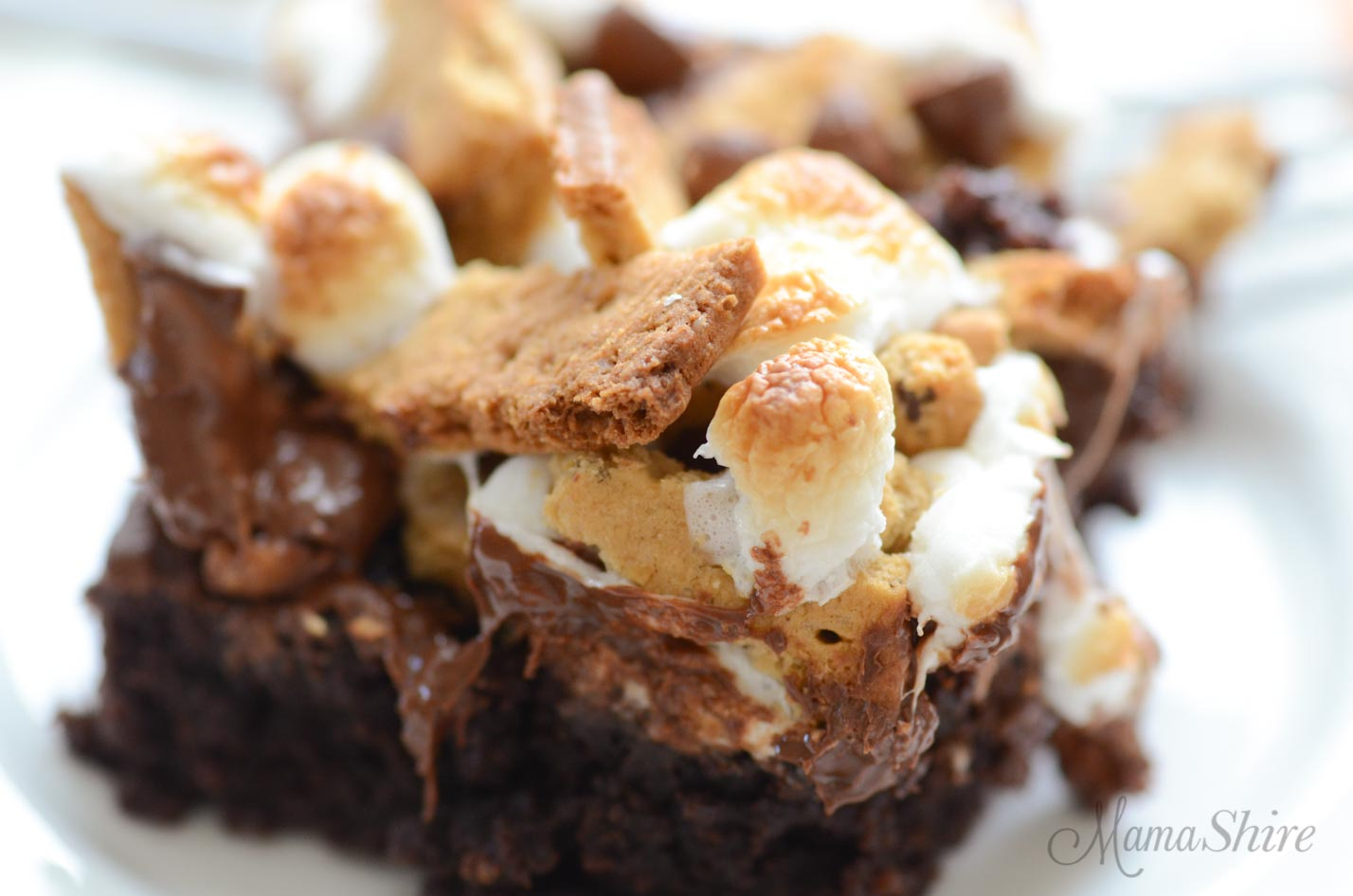 Melting chocolate and roasted marshmallows cover a gluten-free s'mores brownie.