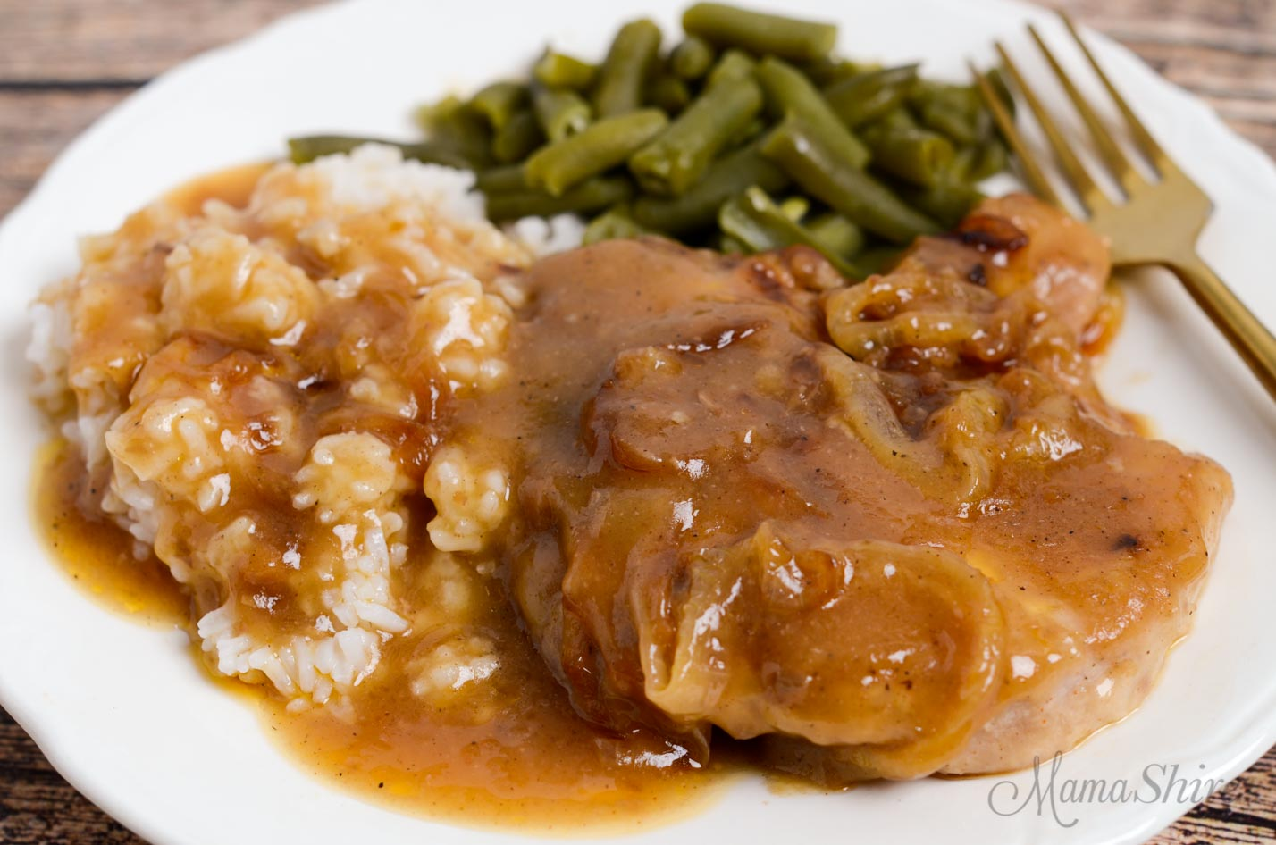 A dinner plate with smothered pork chops and rice with serving of green beans.