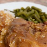 A dinner plate of pork chops with onion gravy and a side of rice and green beans.