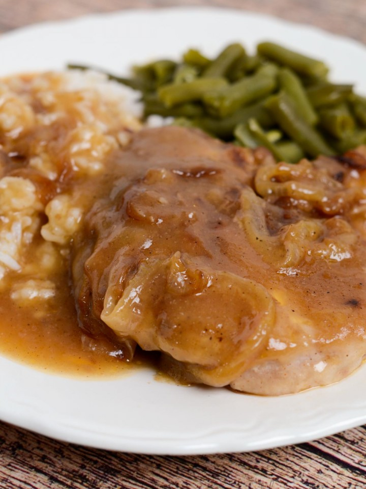 A vertical picture of a white dinner plate with a pork chop that has onion gravy poured over the top with a side of white rice and green beans.