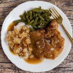 A white dinner plate with a delicious dinner of gluten-free smothered pork chops with a side of white rice and green beans.