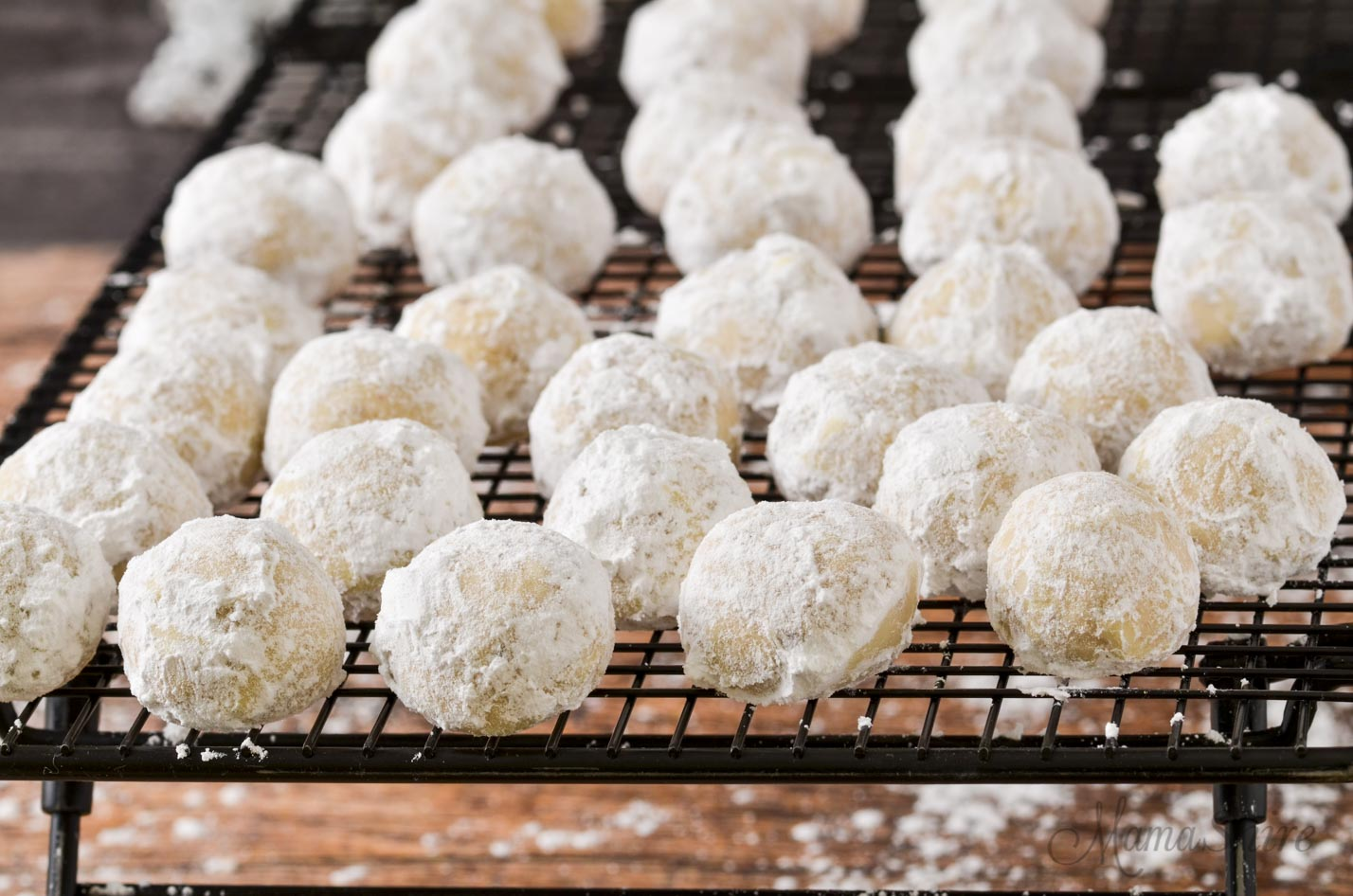 Gluten-free snowball cookies cooling on a wire rack.