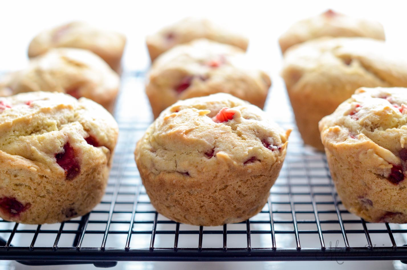 A picture of 9 strawberry muffins cooling on a wire rack.