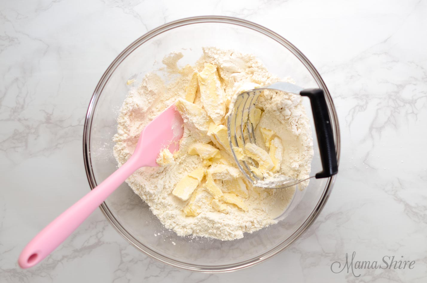 Cutting in buttery spread into gluten-free flour with a pastry cutter.