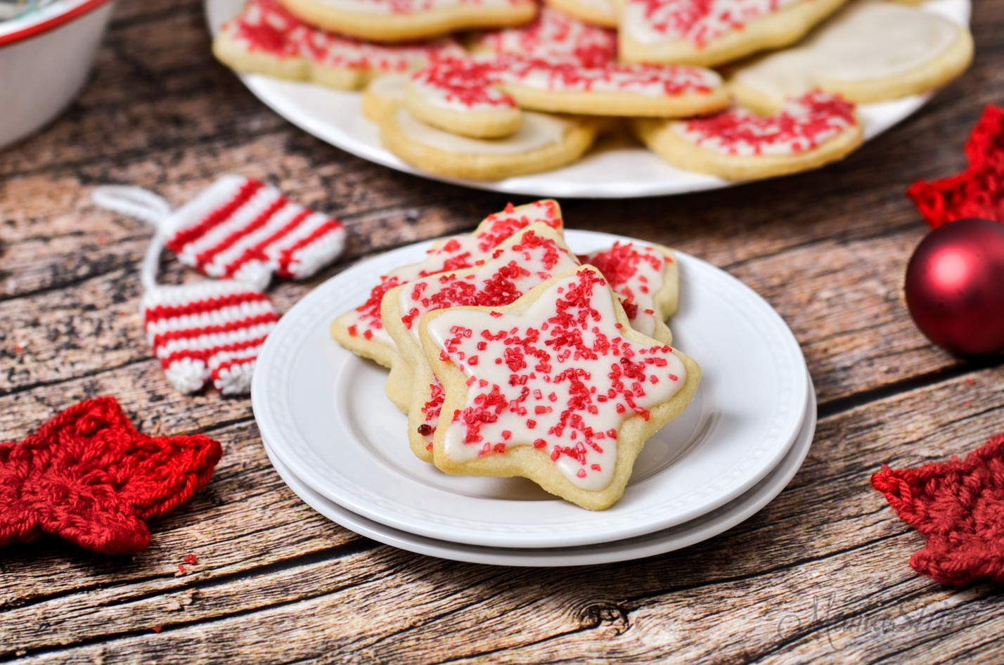 Gluten-free Christmas cookies with dairy-free white icing and red sprinkles.