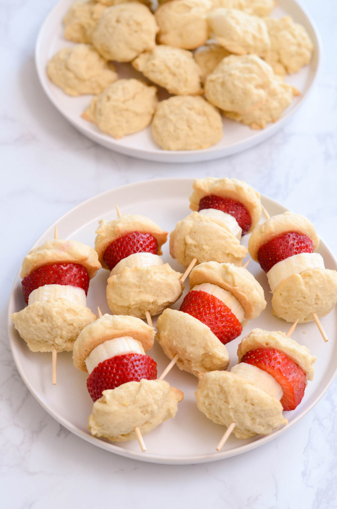 A plate of cookie and fruit skewers.