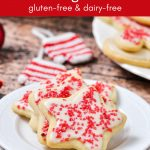 Gluten-free cut-out sugar cookies with dairy-free icing and red sprinkles.