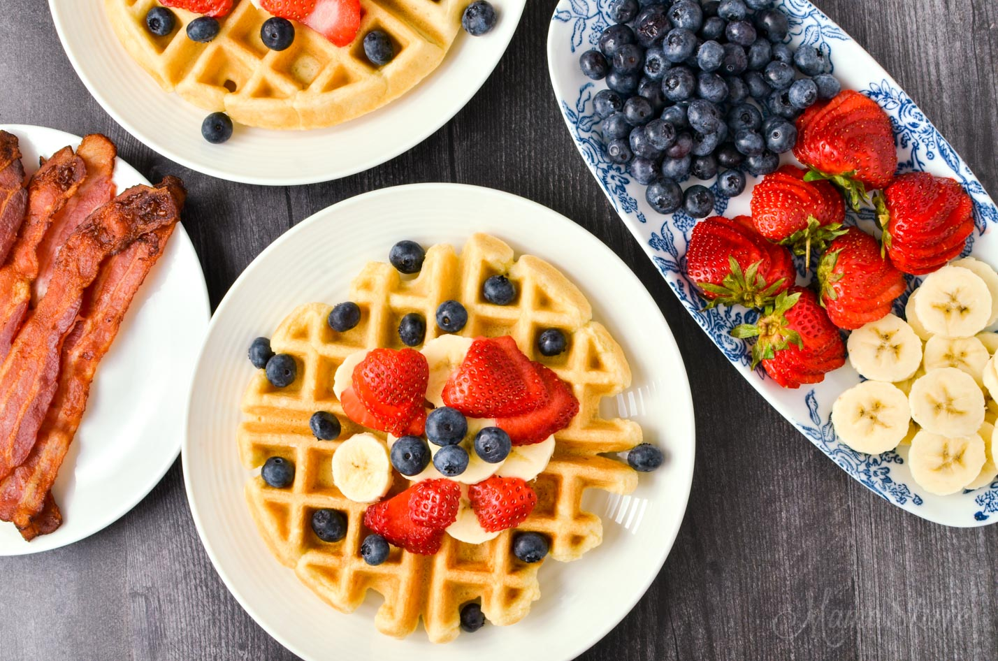A breakfast buffet with waffles, bacon, and fruit.