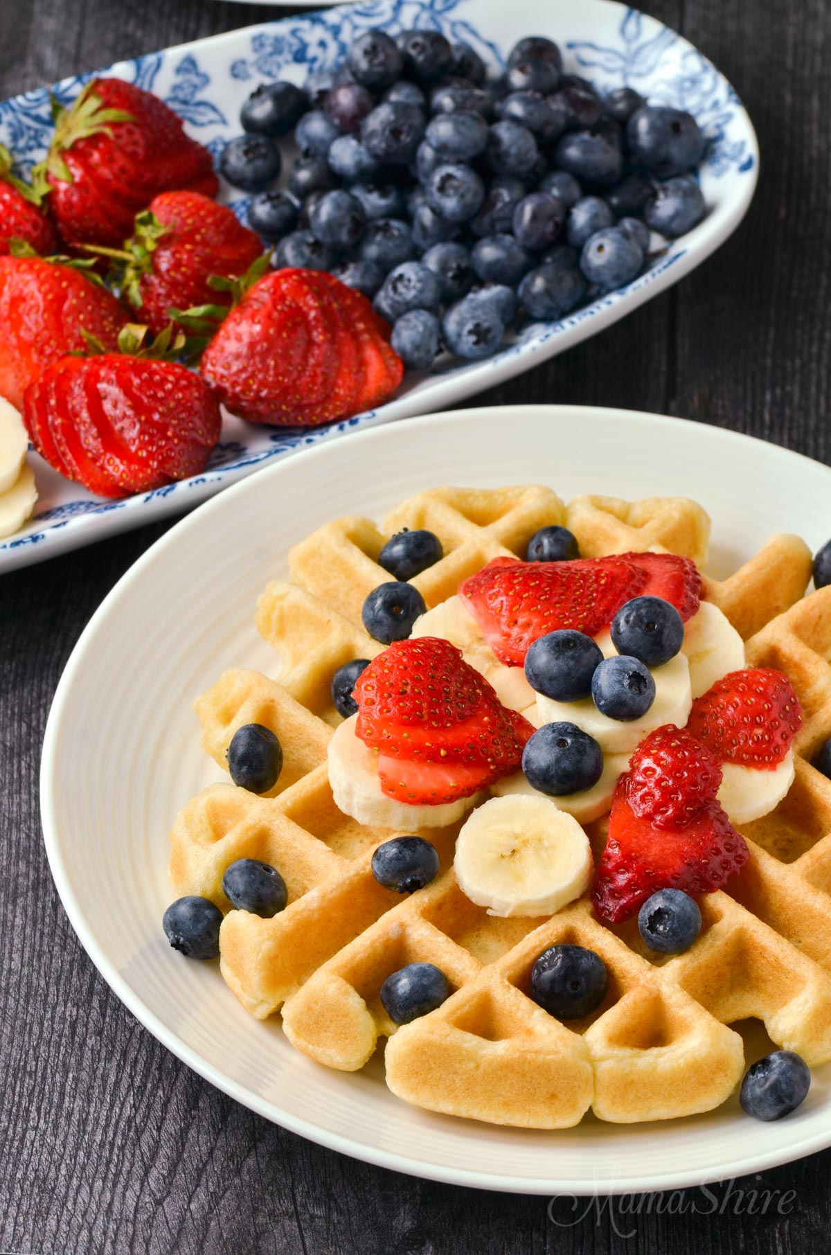 Waffles with bananas, strawberries, and blueberries.