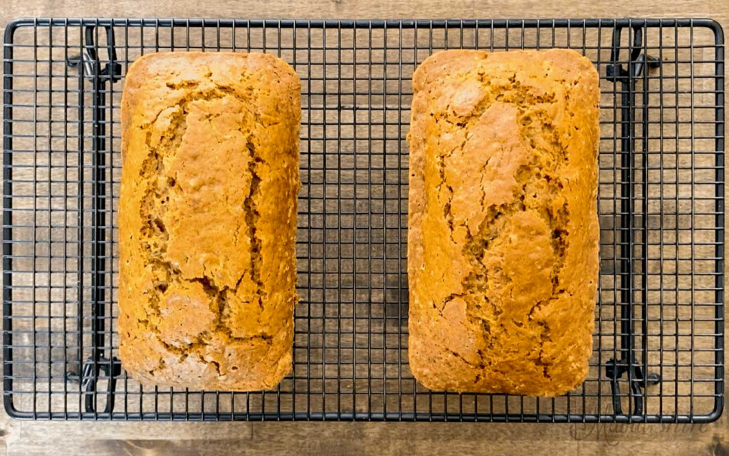 Two freshly baked gluten-free zucchini bread loaves sitting on a wire rack to cool