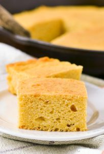 Gluten-free cornbread on a white serving plate with a cast-iron skillet of cornbread in the background.