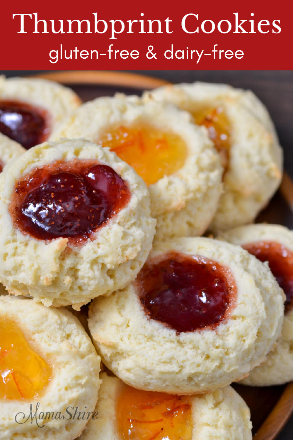 A closeup of gluten-free thumbprint cookies with orange marmalade and strawberry jam.