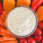 Homemade dairy-free ranch dip served with tomatoes, carrots, and peppers.