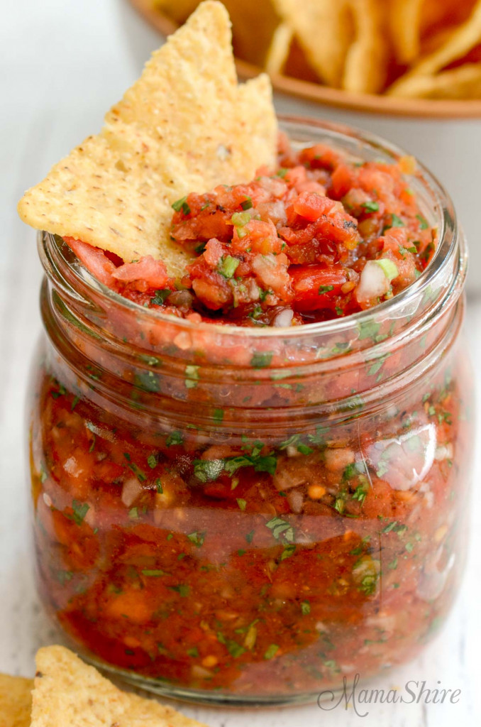 Easy homemade salsa in a ball jar with a couple of tortilla chips sticking out.