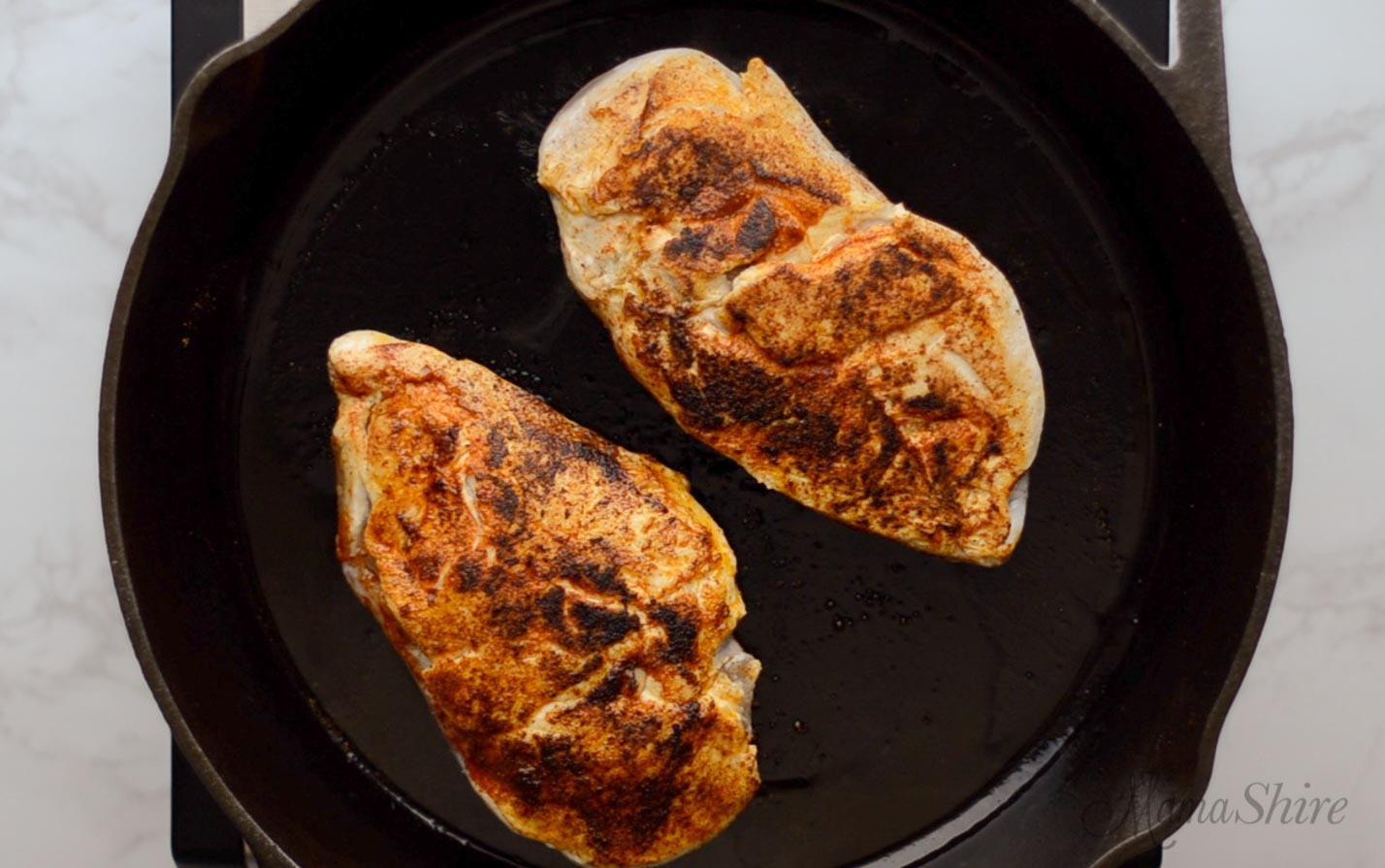 Searing seasoned chicken in a black iron skillet.