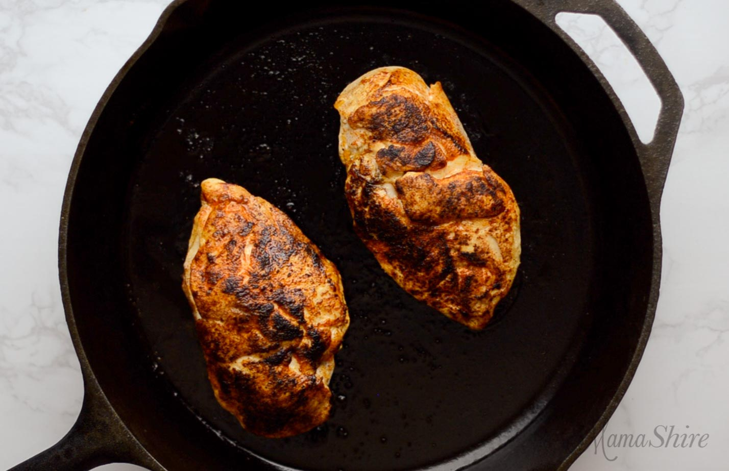 Two chicken breasts that have been seasoned in a black iron skillet.