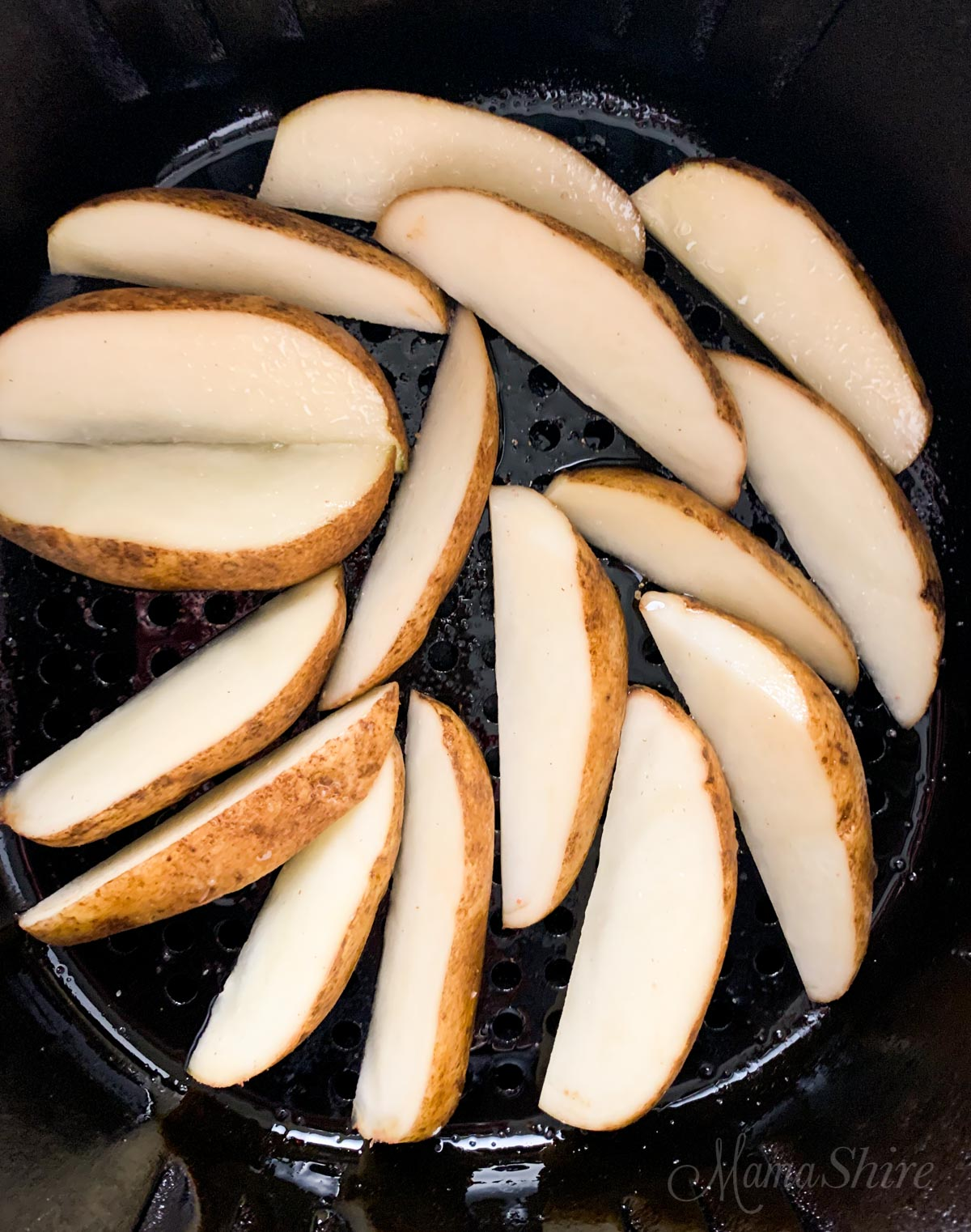 Potato wedges in an air fryer.